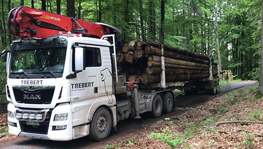 Dieses Bild zeigt einen Sattelzug mit Kran beim Holztransport